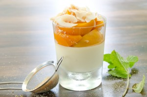 Some peaches in a glass jar with cream & sugar