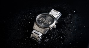 A silver watch on black background with wayer drops