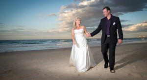 A wedding couple holding hands on the beach