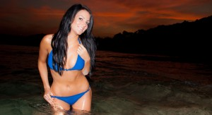 A young brunette posing in a blue bikini at sunset