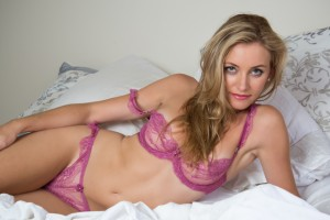 A blonde sexy girl lying on a bed in pink bra & panties