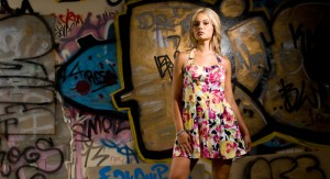 a blonde girl in front of a graffitti wall