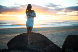 Sunrise image of girl in white dress standing on a cliff